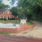 The Exterior of the Rosevine Inn Bed and Breakfast. A two story brick building with a brick clock towner and american flags