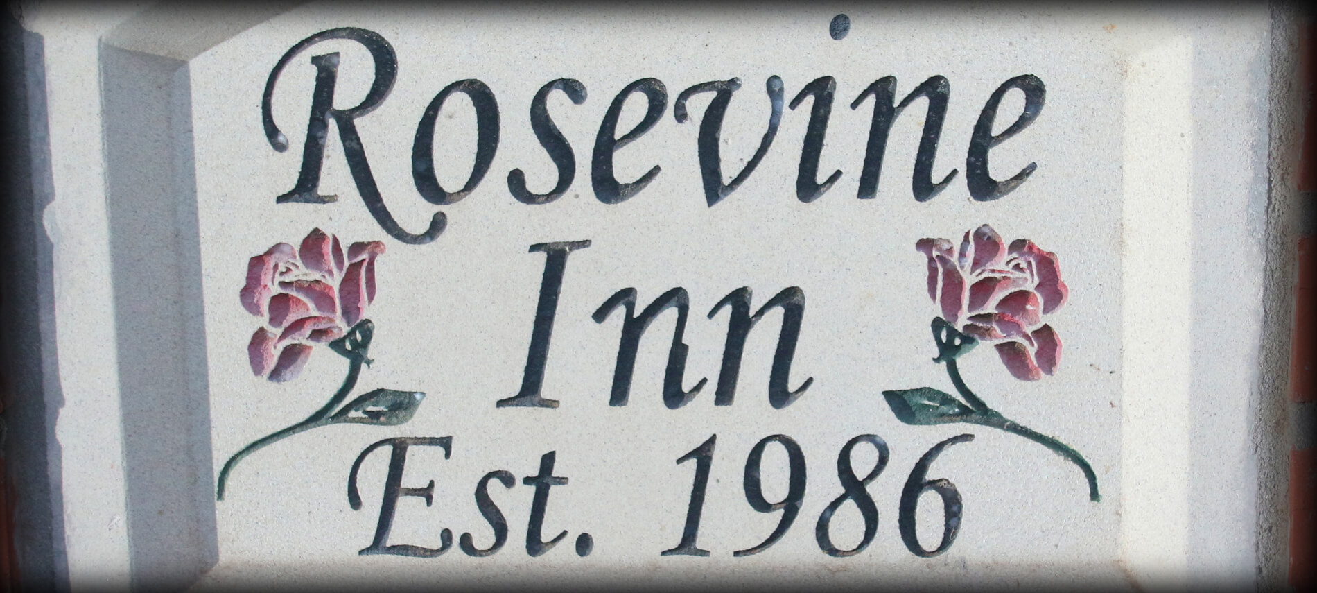 Rosevine Inn Creme Plaque that says Rosevine Inn established 1986 with 2 red roses etched on either side