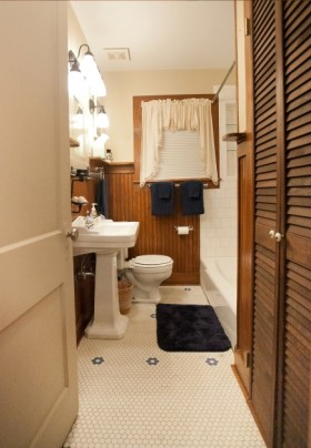 Bathroom with small octagonal tile on the floor, large rectangular tile backing the tub/shower combo, and stained beadboard accenting the walls