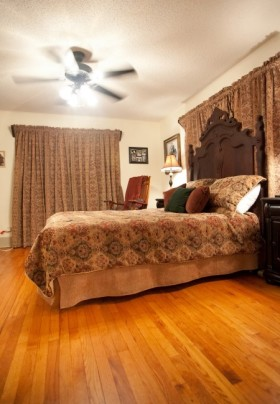 Bedroom featuring ornate high back bed with golden tapestry spread