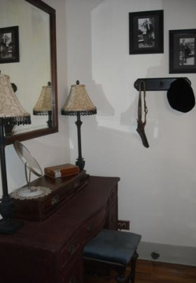 Antique vanity and stool with lamps and mirrors on it and a coat hook on the wall behind it