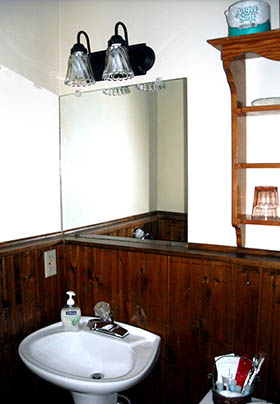 Bathroom with pedestal sink in front of stained beadboard walls