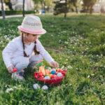 Cute little four year old girl enjoying Easter egg hunt in a public park
