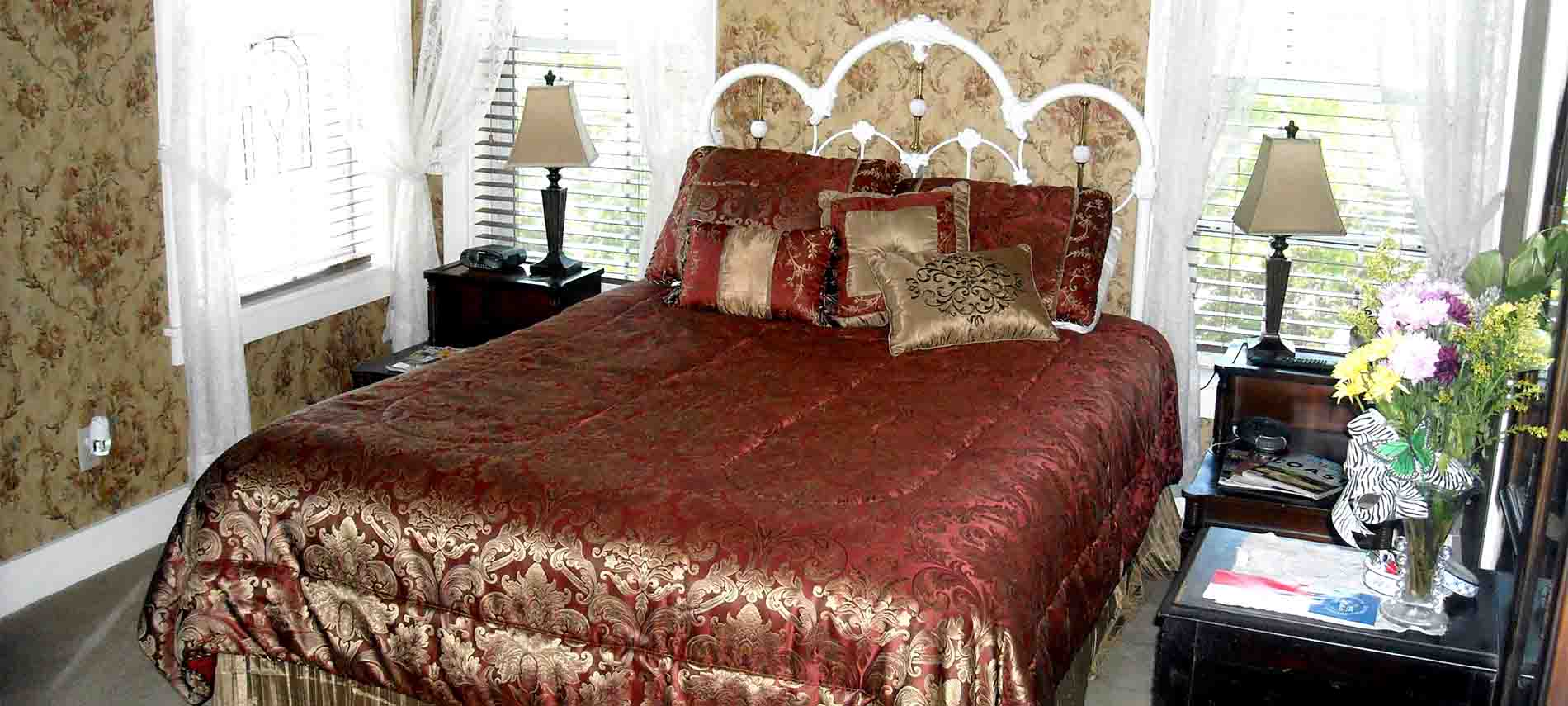 Bluebonnet Room with floral wallpaper, a white iron bed covered with a red and gold satin spread, and flanked by two nightstands and a vanity