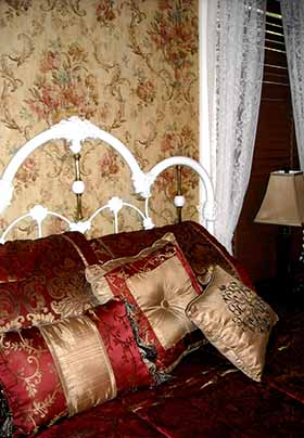 : Close-up of bed in Bluebonnet room showing white iron headboard with red-and-gold pillows leaning against it