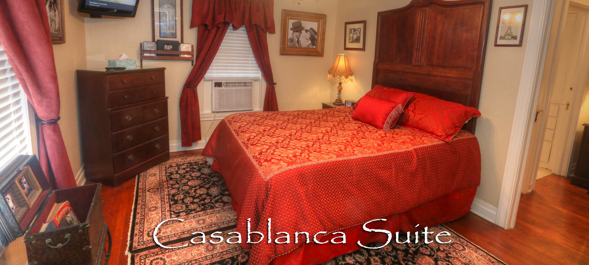 Red and Gold Bedspread with a window unit, tv and brown dresser drawers