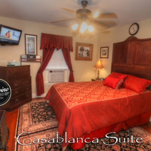 Red and Gold Bedspread, window unit, tv and brown dresser drawers