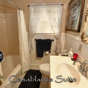 Bathroom with Navy Blue Towels, a comomde, sink and tub with shower