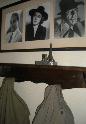 Closeup of coat rack with two trench coats hung on it. Over top is a photo with three headshots of the stars of the movie Casablanca