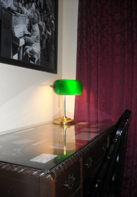 Flat top writing table with bentwood chair and classic green-shaded brass desk lamp