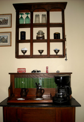 A coffee pot sits on a wooden buffet with green tile backer and marble top. Above it is a wall mounted window-box style shelf with assorted drinkware