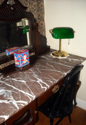 Close up of marble topped dresser with bentwood chair, classic brass and green hooded desk lamp, and Union Jack styled tea canister