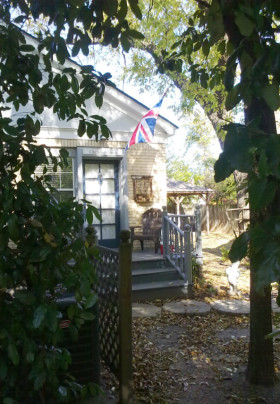 Entrance to the Churchill Room through a treed archway. A Union Jack flies over the deck