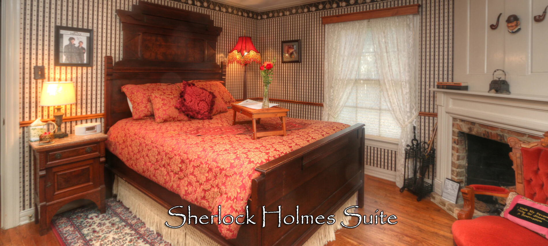 Sherlock Suite with high-back wooden bed covered in red comforter with lap tray and flowers