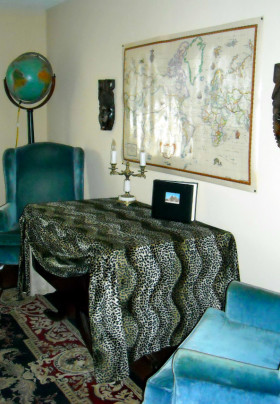Table covered in leopard print fabric flanked by two teal wingback chairs