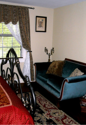 Blue Duncan Phyfe style sofa at the end of a wrought iron bed frame