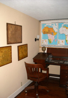 Captain's Desk and wooden office chair flanked by world maps from various time periods