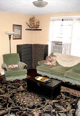 Living room with mint colored sofa and chairs set on black and gold oriental rug. Behind them are an open steamer trunk and model sailing ship