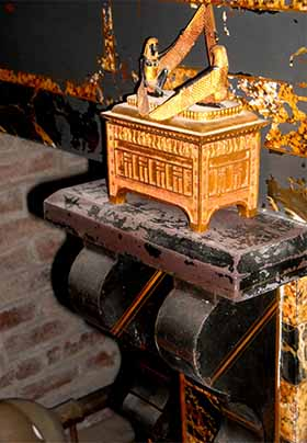 Close up of black and gold marble fireplace with ark of the covenant statuette