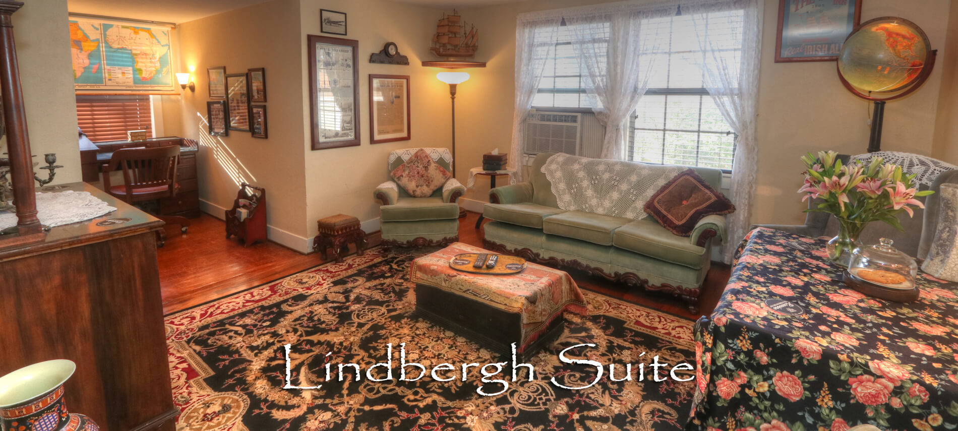 Vintage Living Room in the Lindbergh Suite with Green couches and antique wall hangings