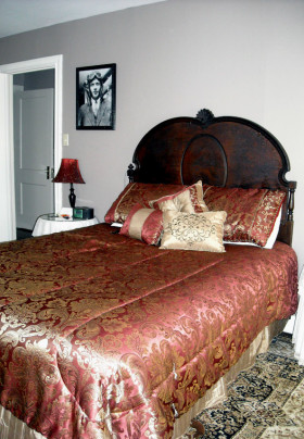 Queen bed with wooden headboard and red coverlet with gold accent. Photo of Charles Lindbergh on the wall