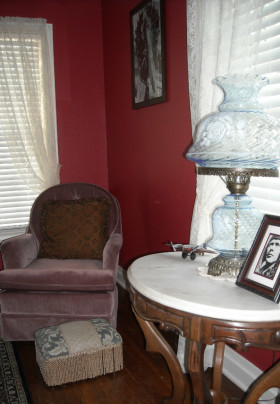 Pink occasional chair set in a corner next to marble top hall table with glass lamp and historic photo of Charles Lindbergh