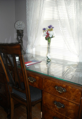 Glass topped desk of burled wood with Queen Anne style chair and glass art nouveau lamp