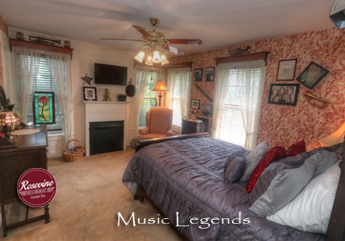 An upstairs bed and breakfast room with red and creme wall paper, a dark brown highback bed with a blue duvet. Also in the room is a pink fabric chair and brown ceiling fan