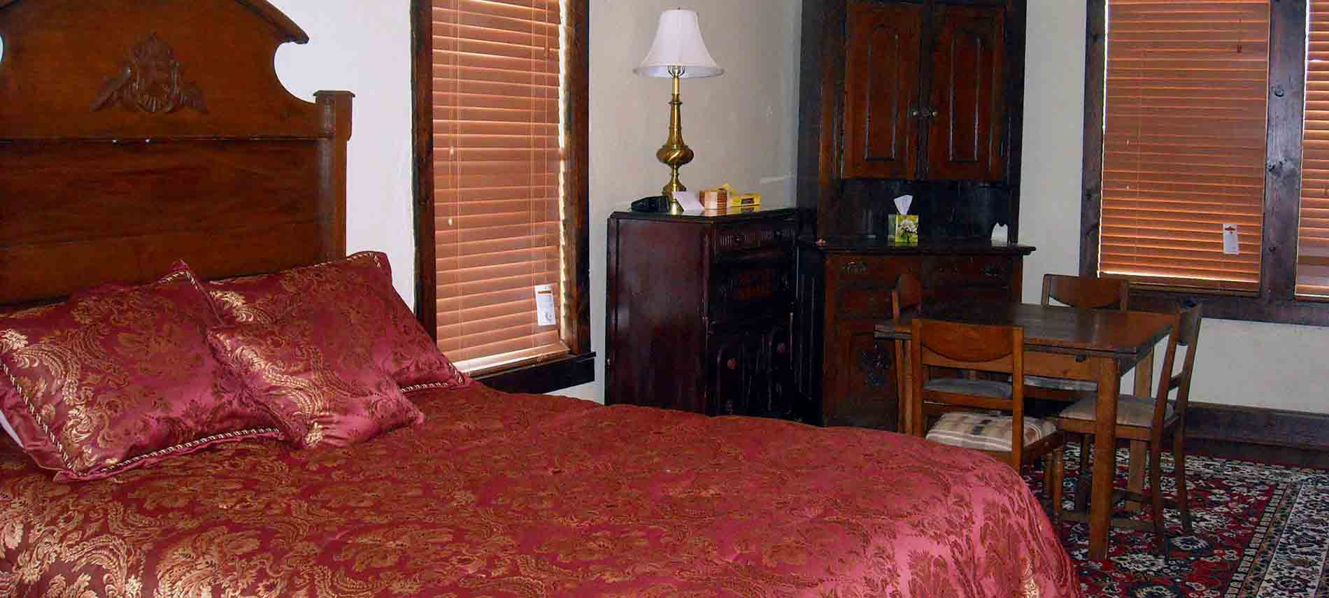 : Single Room Suite with the bed's wooden headboard and red-and-gold embroidered coverlet in the foreground and Depression-era drop-leaf dining table, and Hoosier cabinet in the background