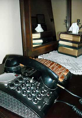 Close up of unique vintage office phone with push-button numbers, speaker screen, and wood and glass accents
