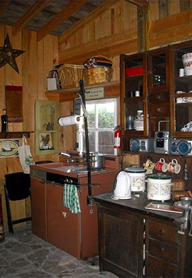 Coffee-station kitchenette in the barn has vintage camp-stove with built in sink and Hoosier cabinet with kettle, mugs, and slow cookers
