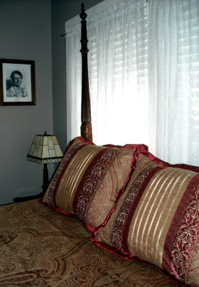 Closeup of Spindle Bed with gold and red cover and pillows. Photo of Eleanor Roosevelt on the wall