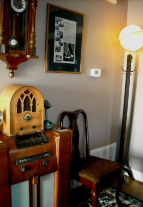 Two old fashioned radios circa 1920s-1930s with Vienna wall clock, Queen Anne dining chair, and globe lamp