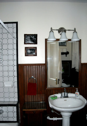 Bathroom with vintage tile, stained beadboard walls, and white pedestal sink