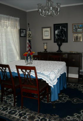 Dining room table with blue tablecloth topped with white lace surrounded by Sheraton style chairs. Buffet in back with photos of Theodore Roosevelt on wall