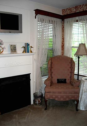 Pink wingback chair set next to table by corner windows and mock fireplace in Rose Room