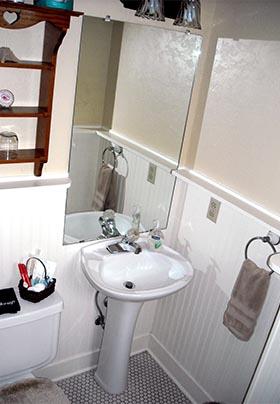 Bathroom showing pedestal sink set on vintage octagonal tile with white beadboard walls