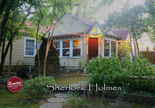 Sherlock Holmes Cottage with yellow siding, brown door and green foresty foliage