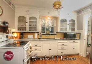Sherlock Holmes Kitchen with white oven stove, white cabinets, kitchen sink, fridge and microwave