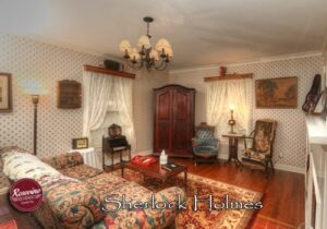 Sherlock Holmes Living Room with rug, couch, blue chair and tv cabinet