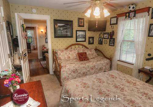 Sports Legend room with floral striped wallpaper, brass Queen bed with white satin spread, and antique dresser with mirror