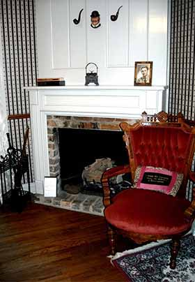Fireplace in Sherlock bedroom with carved Louis XVI chair set next to it
