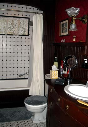 Victorian style bathroom with rich wood walls, black-and-white tile floors, and deep tub with tile surround