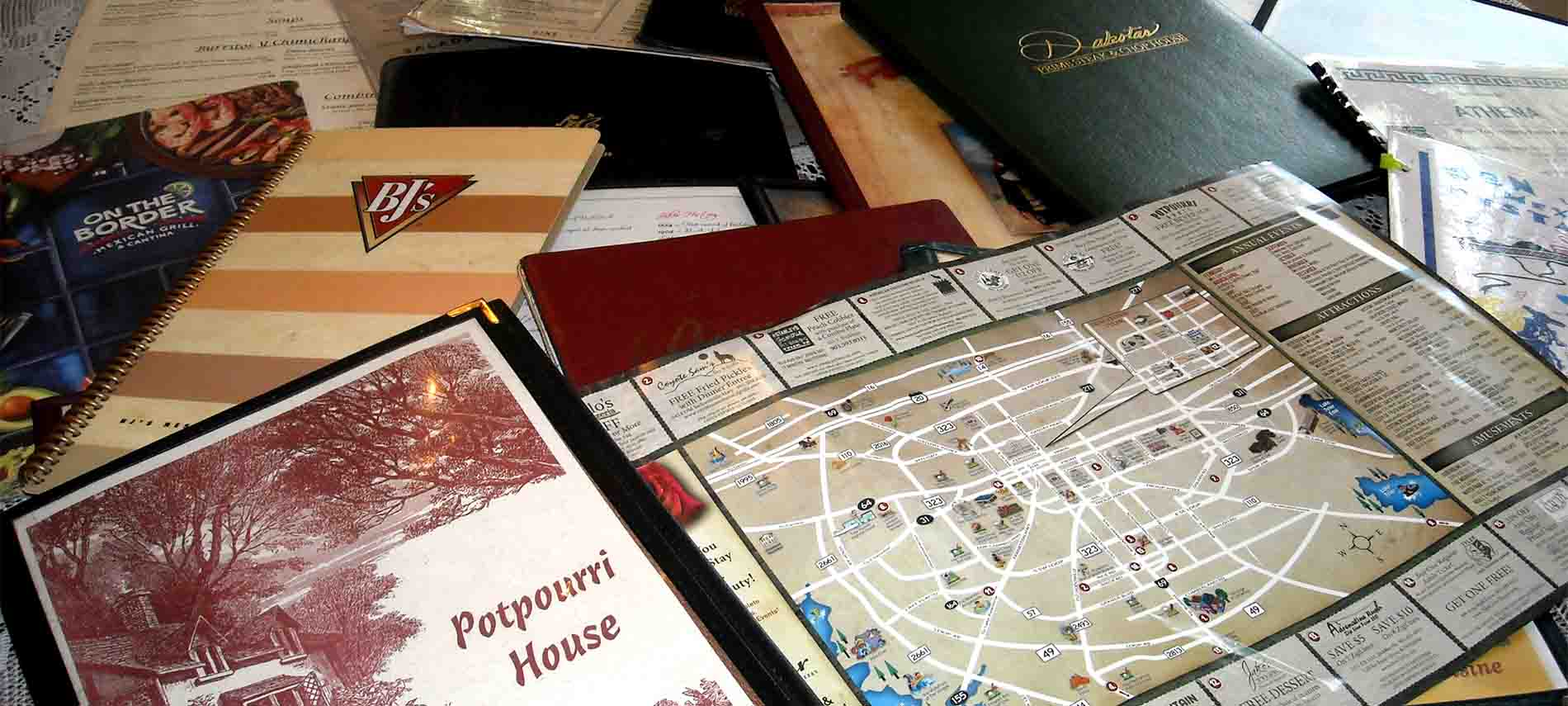 Close up of local menus and area map spread on the lace-topped breakfast table