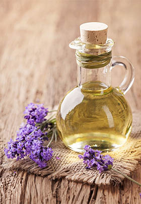 Close up of massage oil in glass bottle with lavender flowers and burlap coaster