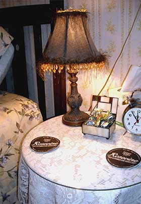 Close up of bedside table in Sunshine Room showing lamp, classic alarm clock, candy dish, and coasters with the inn's logo