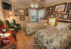 Texas Legends room with two twin beds, dresser, and green wingback chair