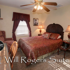 Highback bed covered in red comforter with gold accents. Photo of Will Rogers on the wall