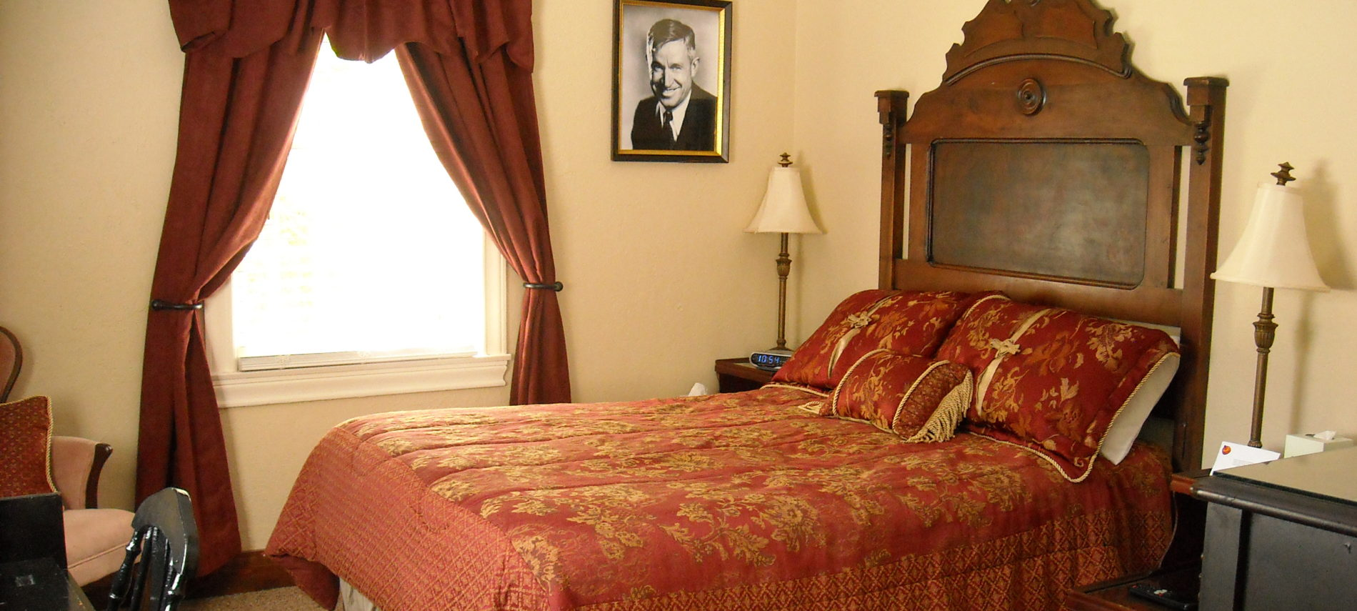 Wooden highback bed is topped with black and gold coverlet. The walls around it feature screen shots from the movie Casablanca and Parisian themed wall art