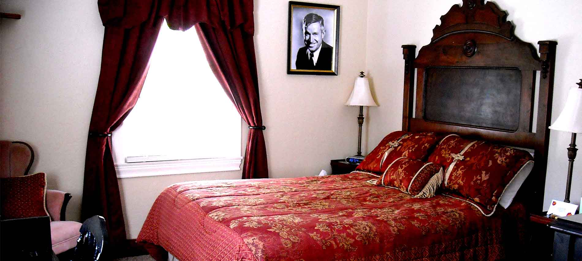 Bedroom with highback bed covered in red comforter with gold accents. Photo of Will Rogers on the wall